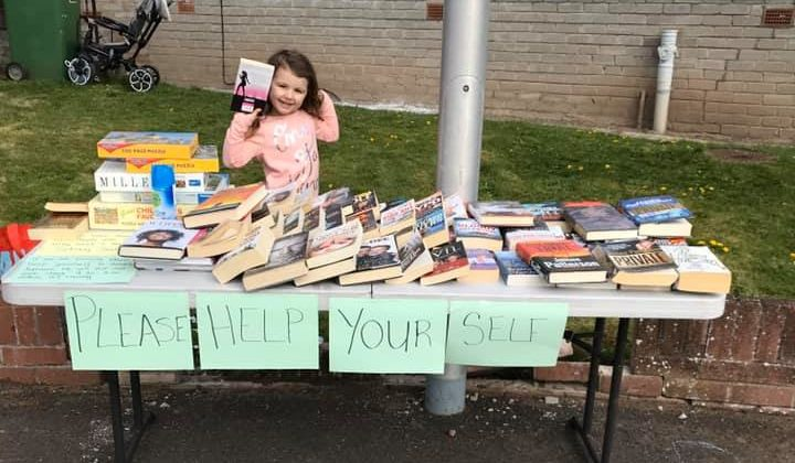 Indie and her mum Sam have a book stall outside their house.