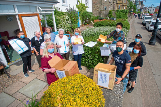 Staff and residents gratefully accept the donations of meals and PPE from staff and owner of The Manchurian.