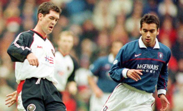 Falconer moves the ball away from former Rangers star Giovanni van Bronckhorst.