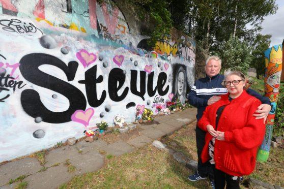 Derrick Murdoch and Sharron Stewart, beside the mural to their late daughter, graffiti artist Stevie Murdoch, who died of cervical cancer.