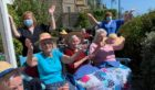 Residents enjoying the performance in the sun.