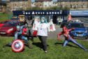 Manager of the food larder Caitlin Baines with the superheroes.
