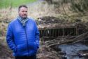The Courier, CR000613, News, Graham Brown story, An otter was killed in a road crash after being unable to get through a culvert in Arbroath which was grilled over. Conservationist Ralph Coutts got the council to cut away the grilling to clear the way for future otter movements. Picture shows; Conservationist Ralph Coutts at the culvert which is blocked by a grill and plant debris. Saturday 16th February, 2019. Mhairi Edwards/DCT Media