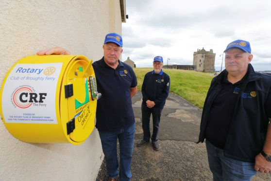 Members of the Rotary Club of Broughty Ferry beside the vandalised defibrillator at the Castle Green Leisure Centre in Broughty Ferry. (Picture: Dougie Nicolson / DCT Media.)
