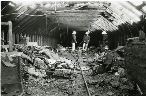 Firemen inspect the damage following the serious fire at the Fountain Disco.