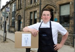 """Dean Banks outside his restaurant with one of the """"Haar at Home"""" boxes."""