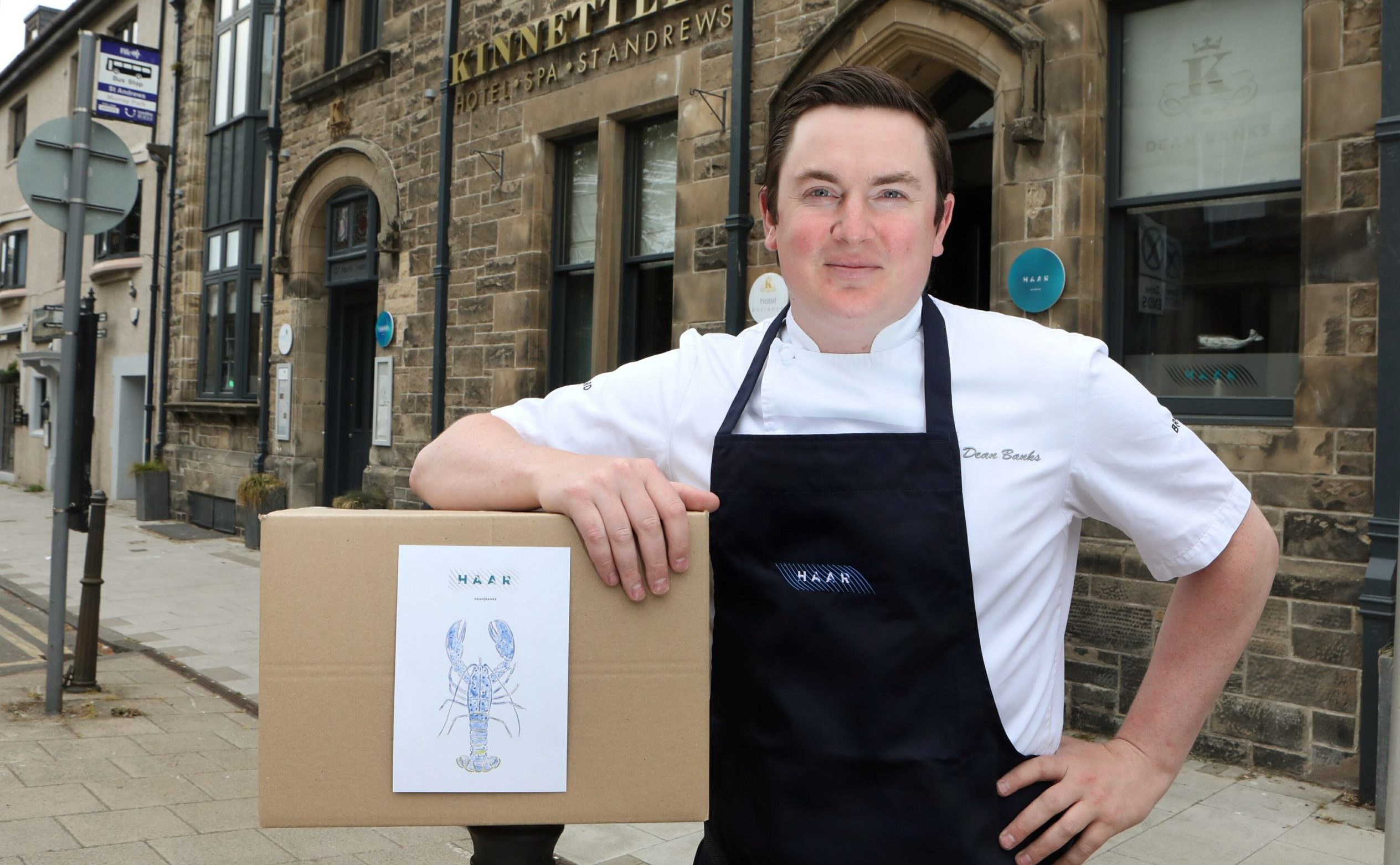 "Dean Banks outside his restaurant with one of the ""Haar at Home"" boxes."