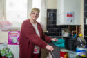 Sharon Andrews in her kitchen with the boiler which is leaking water over the worktop and into the cupboard below the boiler. (Picture: Kim Cessford / DCT Media.)