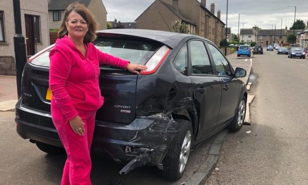 Marilyn Towers next to her damaged vehicle on Balunie Avenue.