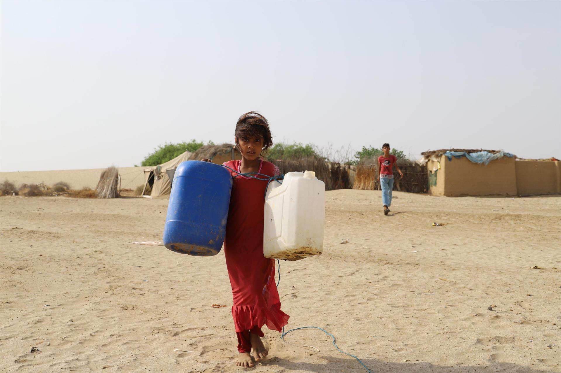 A girl carries empty containers to fetch water in Midi District of Hajjah Province.
