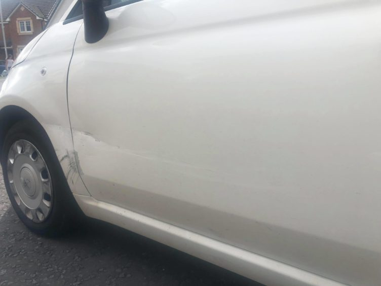 The damage to Rebecca's car.