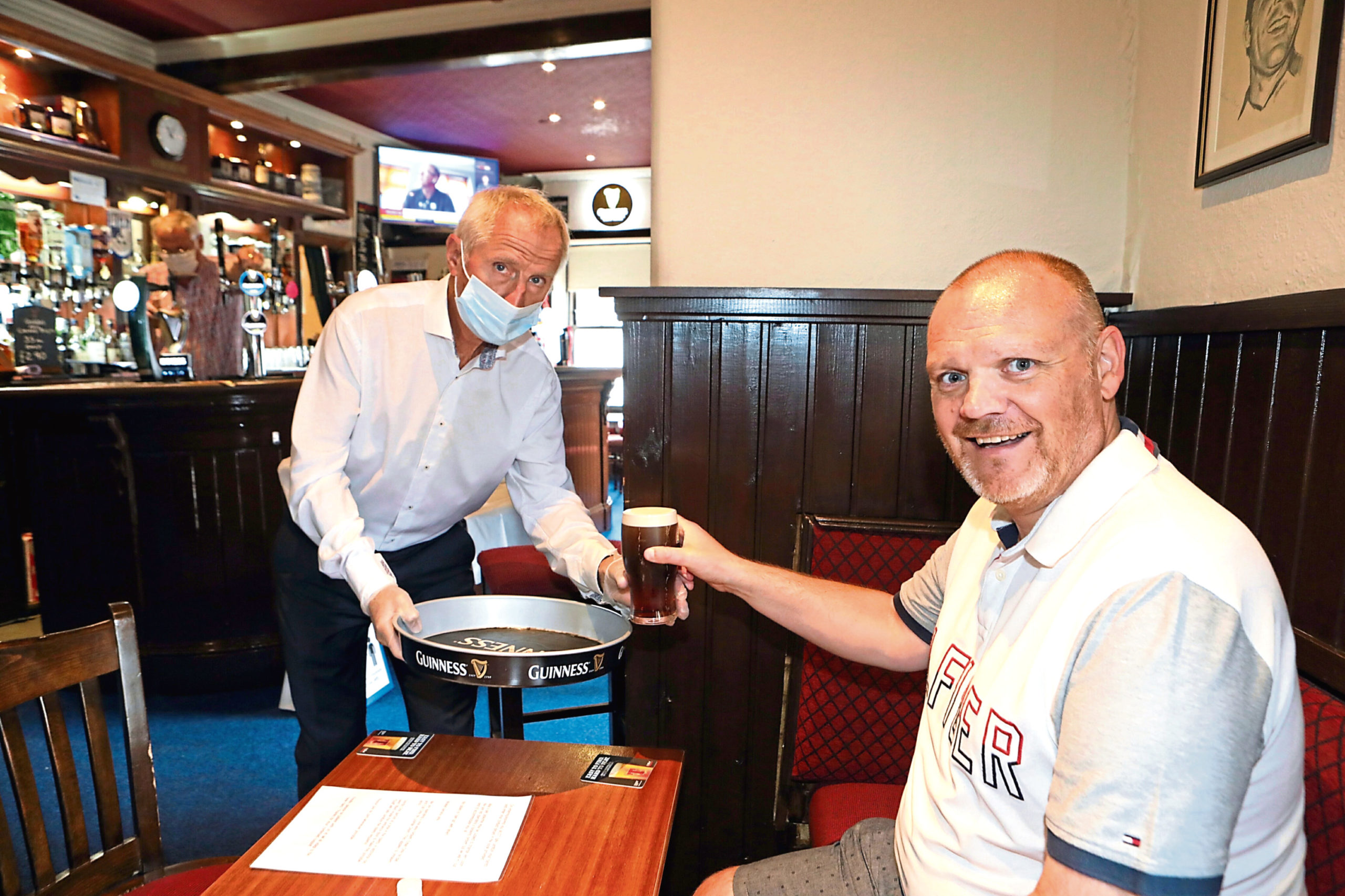 Ronnie Bissell, of the Occidental in Broughty Ferry, serves first customer Paul Gibb.