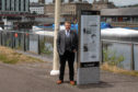 Councillor Alan Ross in City Quay with one of the signs that help make up the trail.