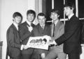 The Beatles holding the sketch with the mystery cartoonist.