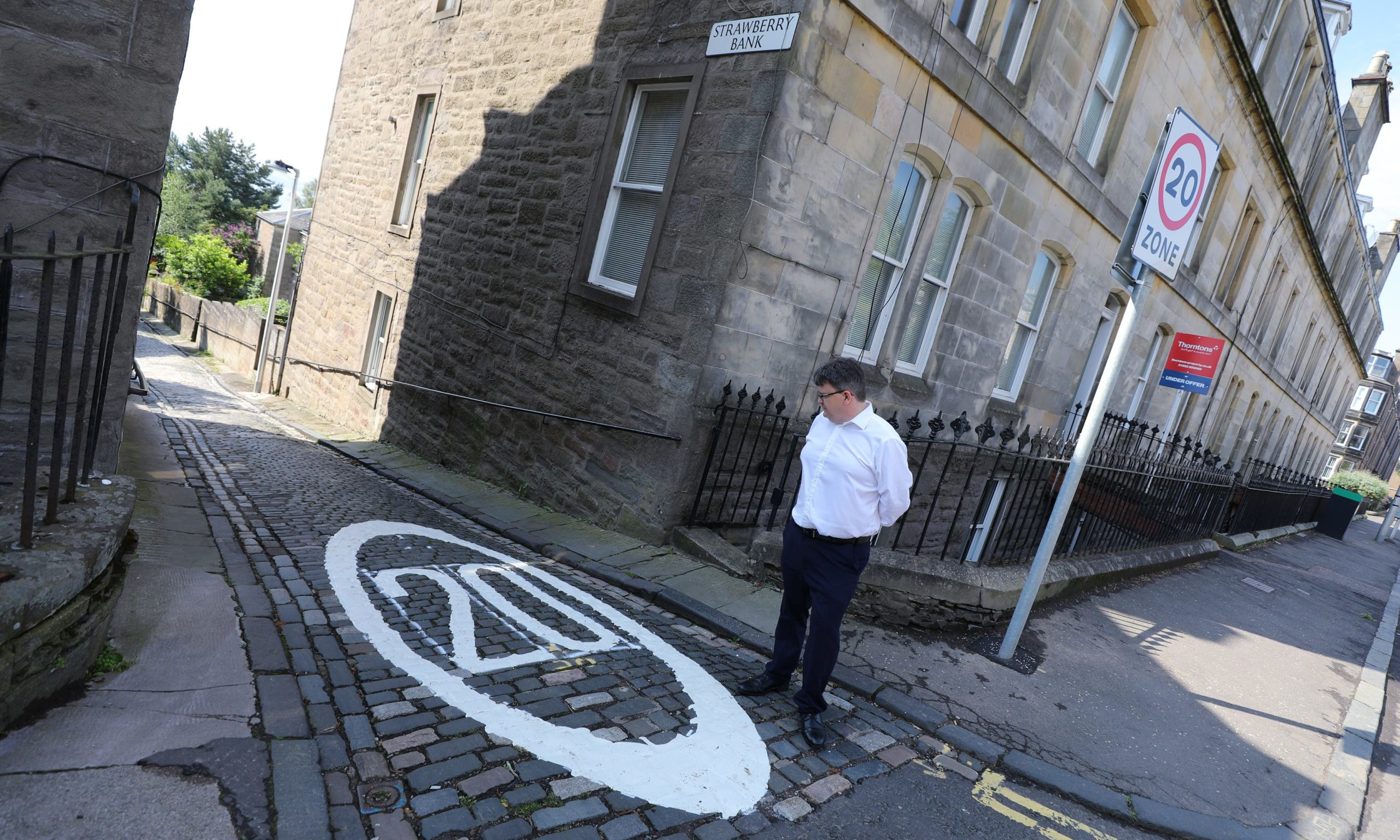 Councillor Richard McCready beside the 20mph sign, which has not been well-received by local residents.