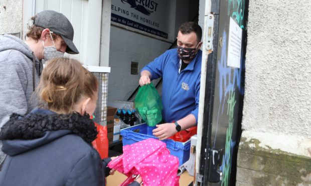 Eagles Wings Trust volunteer Marc Nelson hands out some food bags.