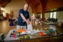 Ross Clark at Fintry Parish Church putting together some food bags.