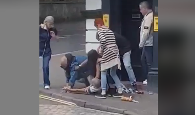 Bags of food scattered outside the Town House Bar as men and woman scuffle on the floor.