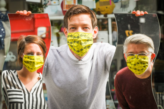 Leader of Dundee City Council John Alexander with, left, illustrator Pamela Scott who designed the masks and co-owner of Quirky Coo, Dave Blair, in the council-endorsed masks.