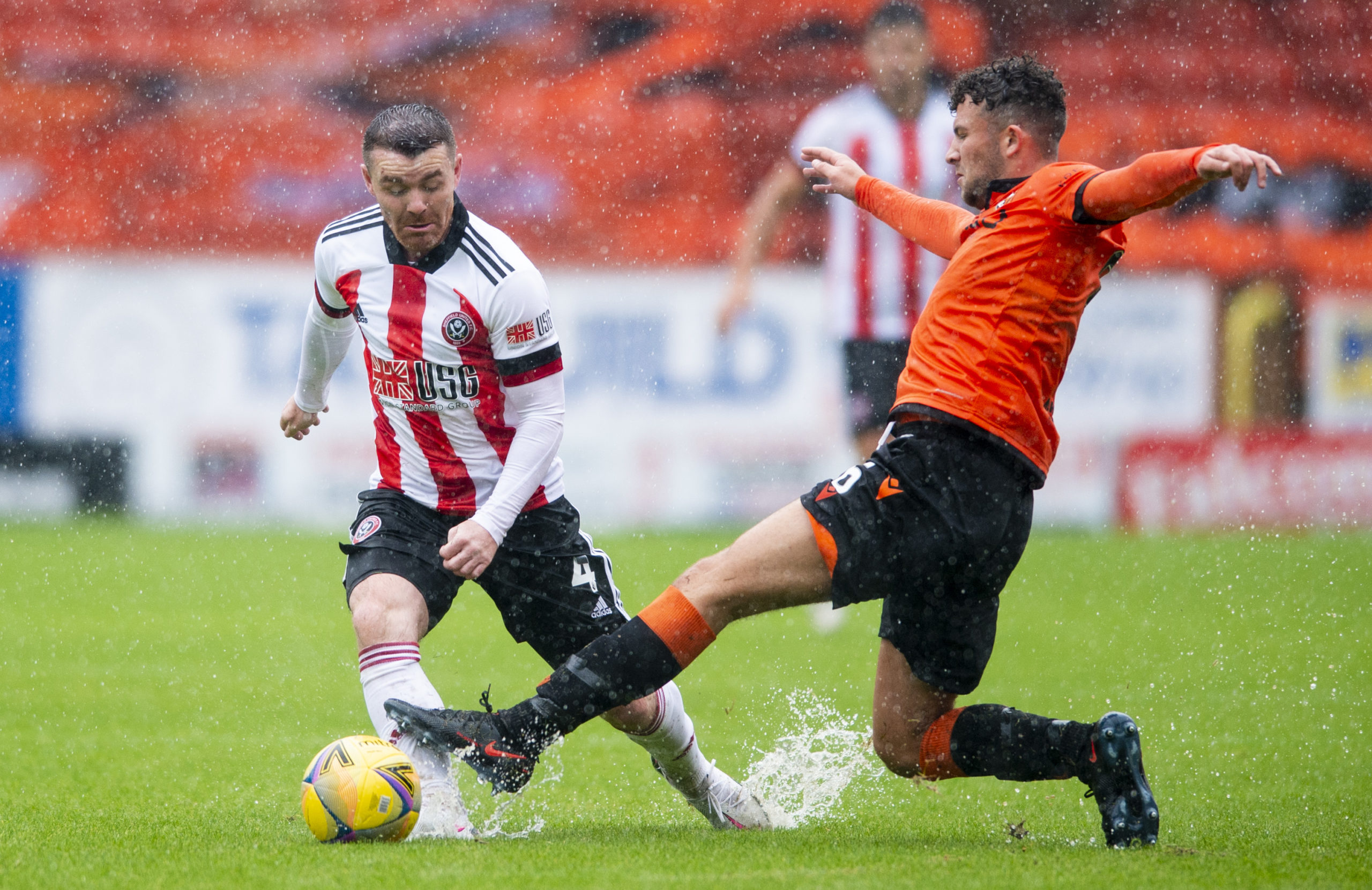 United defender Nathan Cooney challenges Sheffield United and Scotland midfielder John Fleck at a wet and windy Tannadice.