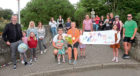 Lauren Simpson ran 200 miles in a month to raise money for Skilz Academy. She is pictured, in the orange top, with friends and family after completing her final run.