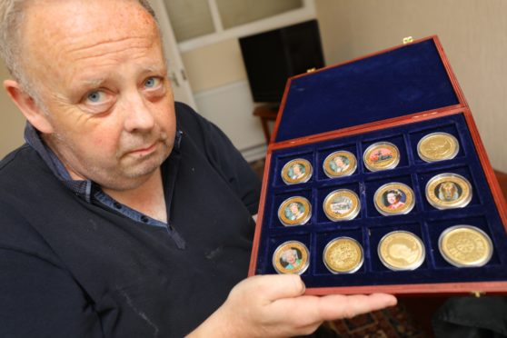Gary Pirie with some Commonwealth Commemorative coins from his collection.