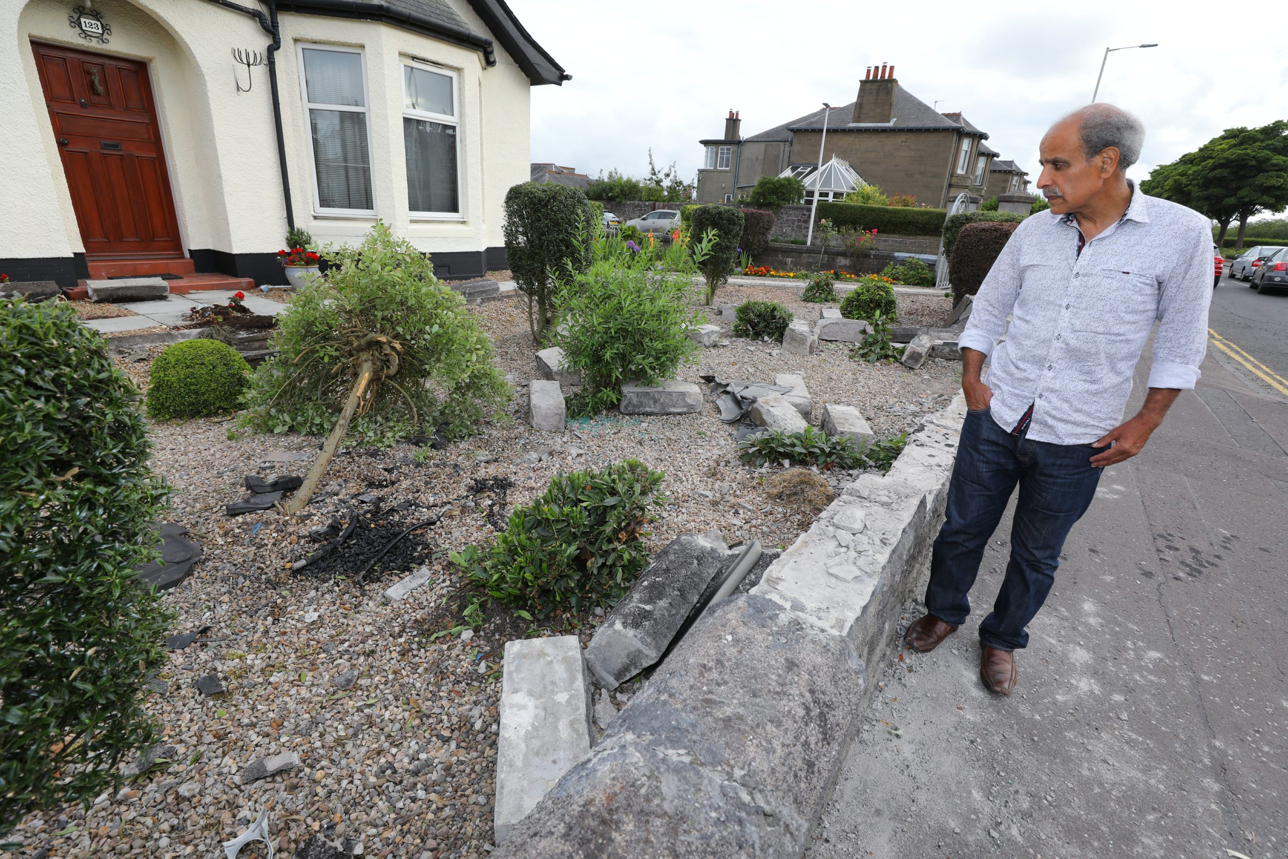 Amgad Taha looking at the damage to the wall of his property on Pitkerro Road.