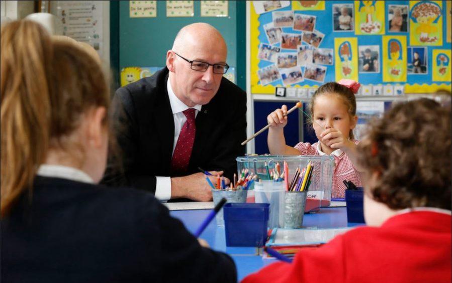 Education Secretary John Swinney helps pupils in school before lockdown.