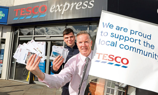 Tesco Strathmartine Road manager Andy Boylen and staff member Matthew Mitchell with the vouchers which are going to Help for KIds.