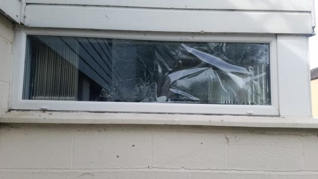 The window was smashed by a group of vandals.