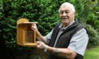 Eddie Piper at home with one of his squirrel boxes, that he has made.