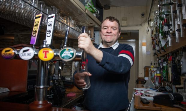 Andrew Hendry pours a pint at GJs Bar and Diner. Picture by Kim Cessford / DCT Media