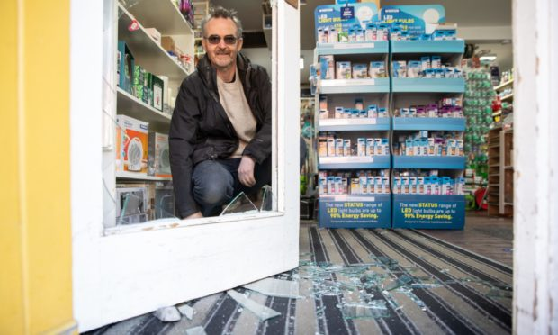 Kenny Watt and the smashed glass from the break-in at the Fobel Shop in Carnoustie. Photo by Kim Cessford / DCT Media