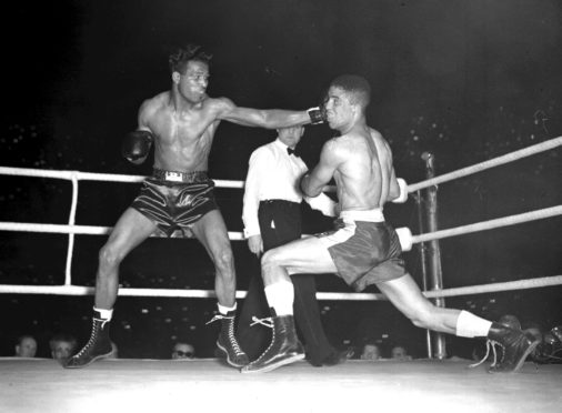 Sugar Ray Robinson (left) throwing a long left to the head of Randolph Turpin during their title bout at Earl's Court in London, in July 1951.