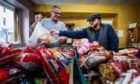 Dundee councillor George McIrvine hands out a food parcel to a service user at HaVeN.