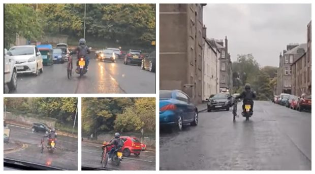 A biker rides a moped while balancing a push bike at a busy junction.