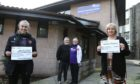 George and Molly Laidlaw, centre, ArabTRUST members, handing over two cheques, each for £719.78, raised through Dundee virtual KiltWalk. The money is being given to Melissa Gormley, left, Community Development Officer, Dundee United Community Trust, and Nikki Lorimer, Locality Leader with Alzheimer Scotland. Photo by Dougie Nicolson/DCT Media.