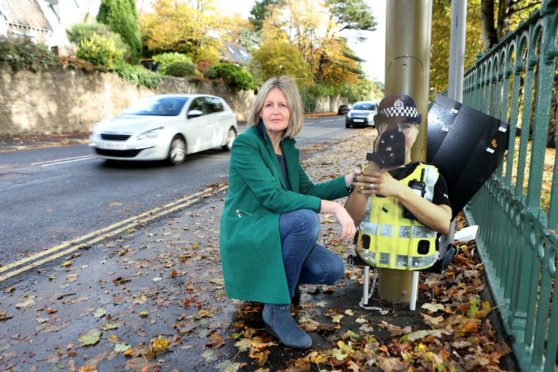 Pop-up Jeane is in two bits, after being  vandalised. Fiona Lund, of Broughty Ferry Community Council, is pictured with the cardboard cop, which the organisation funded.