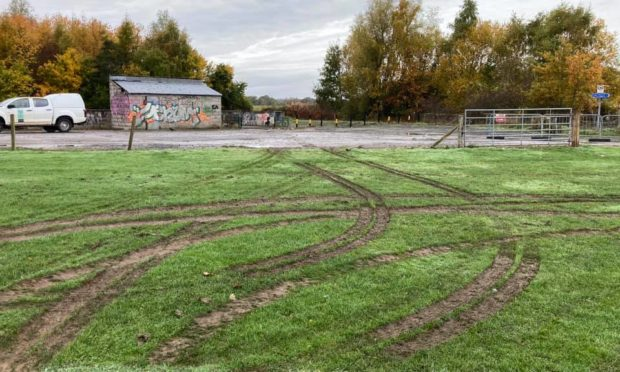 The damage caused by the vandals who drove on the pitch.