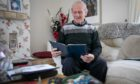 George McGregor looks through some of his photograph collection at home.