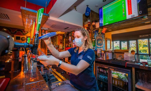 Jo McCormick (shift manager) pours a pint at the  Kilted Kangaroo.