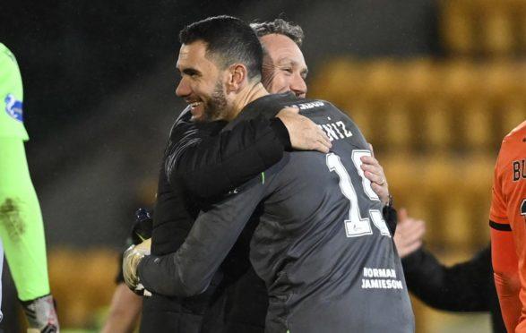United manager Micky Mellon congratulates Deniz after shootout.