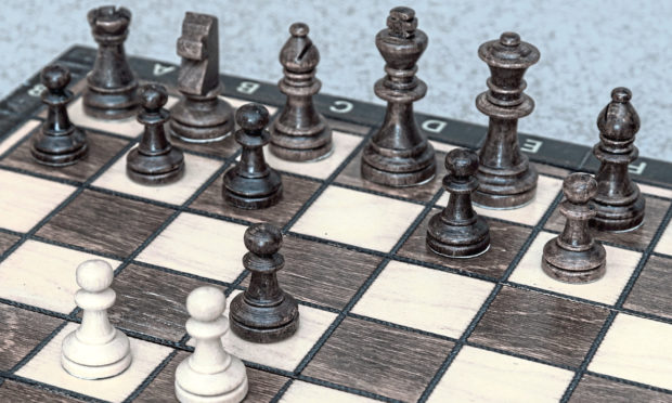 The queen's gambit chess move explained on a chess board.