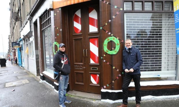 Sykes has transformed the exterior of a building in Stobswell into Santa's Post Office. Symon, left, is pictured with Colin Clement of the Stobswell Forum, whose idea it was to create the letter drop-off point.