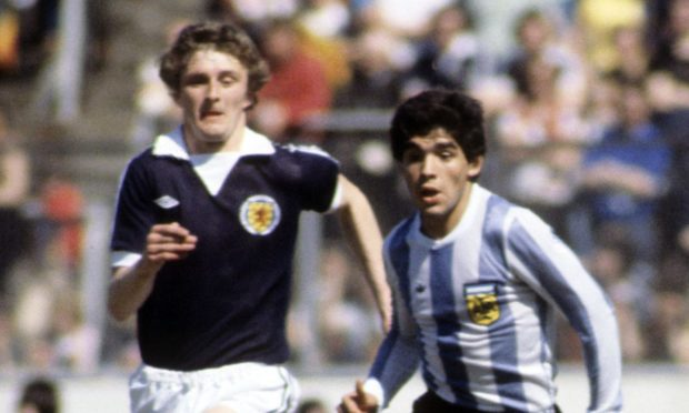 Scotland and Dundee United defender Paul Hegarty attempts to chase down Argentina legend Diego Maradona, who passed away today aged 60.
