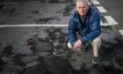 Councillor Craig Duncan with potholes that are to be repaired at the Dunshelt Road and Edzell Street junction in Broughty Ferry.