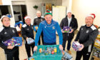 Members of St James walking football team helping John (centre, with hamper) and Jim (second from right) to put the hampers together. The players are (from left) Raymond George, Davie Craig, Daniel McGregor and Steve Carnegie.