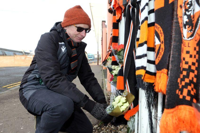 Martin Manzie, 62, lays flowers.