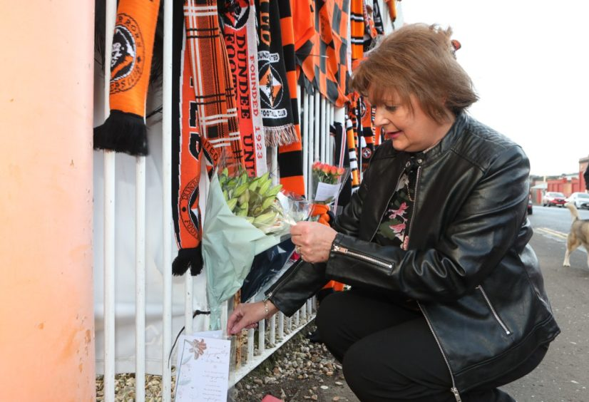 Lynn Coleman leaves flowers at the gates of Tannadice.