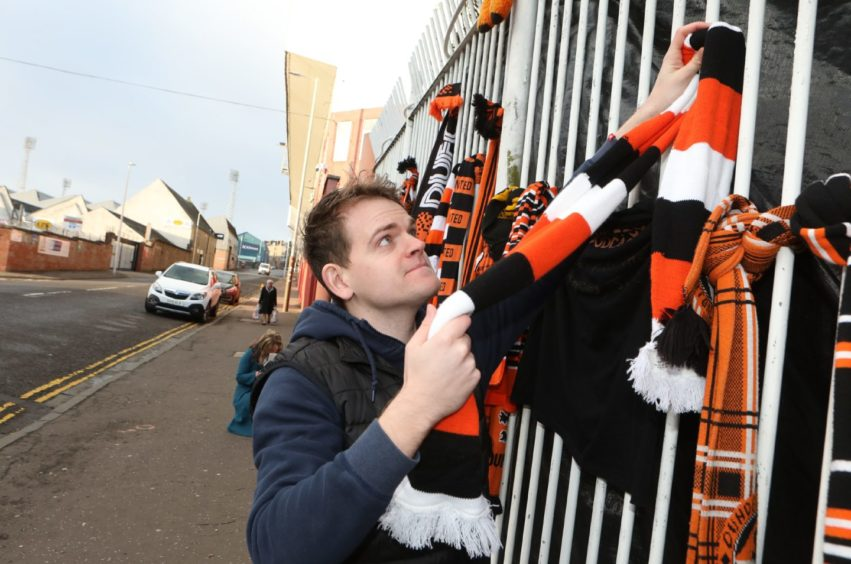 Kris Bissell, 27, ties a scarf on the gate.
